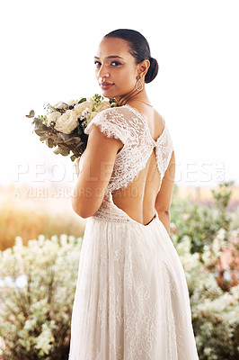 Buy stock photo Portrait of a beautiful young bride holding a bouquet of flowers outdoors on her wedding day