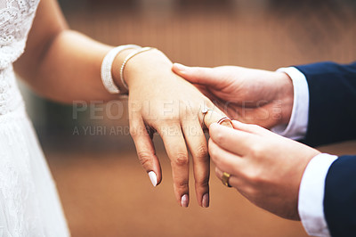 Buy stock photo Cropped shot of an unrecognizable bridegroom putting a ring on his bride's finger on their wedding day