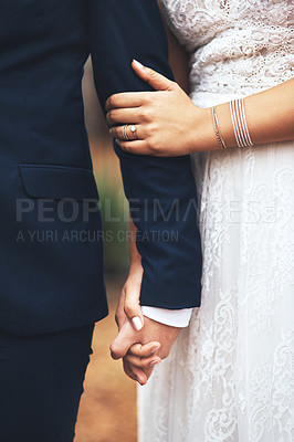 Buy stock photo Cropped shot of an unrecognizable newlywed couple holding hands and walking together on their wedding day