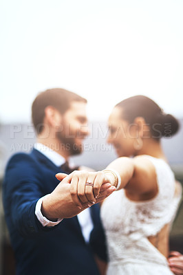 Buy stock photo Shot of a happy newlywed young couple holding hands and dancing together on their wedding day