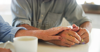 Buy stock photo Cropped shot of a senior couple holding hands while having coffee together at home