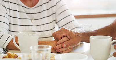 Buy stock photo Cropped shot of a senior couple holding hands while having breakfast together at home