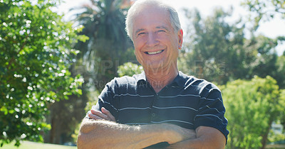 Buy stock photo Cropped portrait of a cheerful senior man smiling while standing with his arms crossed in a park during the day