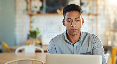 Buy stock photo Cropped shot of a handsome young businessman sitting alone in a coffee shop and using his laptop