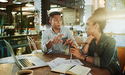Buy stock photo Cropped shot of two young businesspeople sitting together and bonding before discussing their finances in a coffee shop