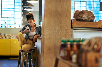 Buy stock photo Full length shot of an attractive young woman sitting alone in a coffee shop and using her cellphone