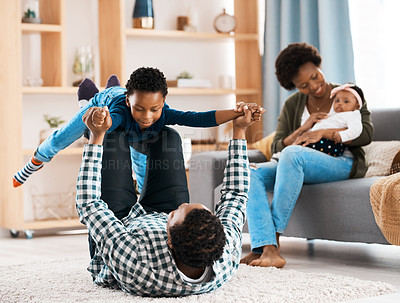 Buy stock photo Shot of a young family spending quality time together at home
