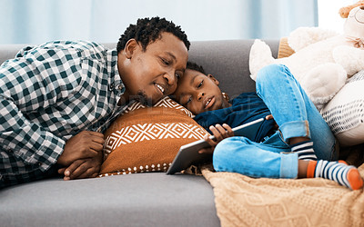 Buy stock photo Shot of a young boy using a digital tablet while sitting with his father