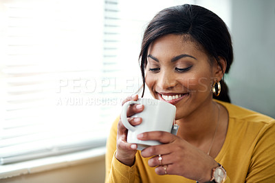 Buy stock photo Cropped shot of an attractive young woman sitting alone and drinking a cup of tea in her home