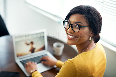 Buy stock photo Cropped shot of an attractive young woman sitting alone in her home and using her laptop