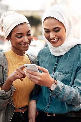 Buy stock photo Cropped shot of two attractive young women wearing headscarves and standing together while using a cellphone in the city