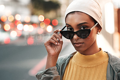 Buy stock photo Cropped shot of an attractive young woman standing alone in the city and looking alluringly over her sunglasses