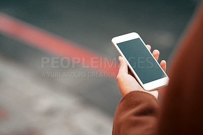 Buy stock photo Cropped shot of an unrecognizable woman standing alone and holding her cellphone while sight-seeing in the city