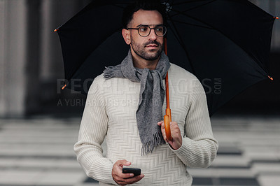 Buy stock photo Cropped shot of a handsome young businessman holding an umbrella while texting on his cellphone outside in the rain