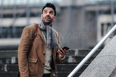 Buy stock photo Cropped shot of a handsome young businessman texting on his cellphone while walking outside in the city