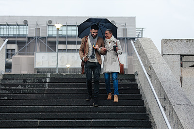 Buy stock photo Cropped shot of a cheerful young couple walking down a flight of stairs while holding an umbrella outside in the rain