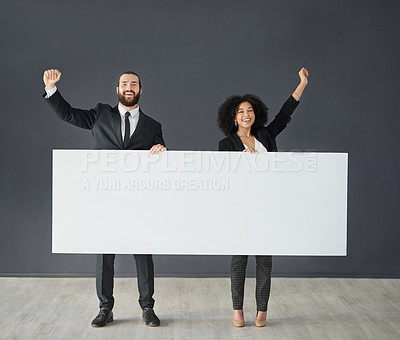 Buy stock photo Full length shot of two young corporate businesspeople holding a blank banner against a grey background