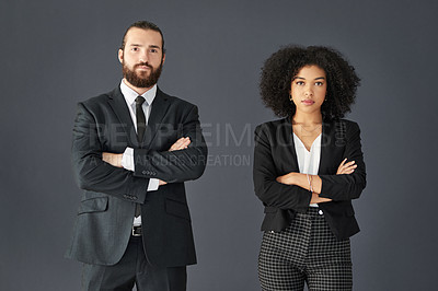 Buy stock photo Studio portrait of two young corporate businesspeople posing together with their arms folded against a grey background