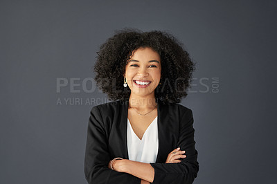 Buy stock photo Studio portrait of an attractive young corporate businesswoman posing with her arms folded against a grey background