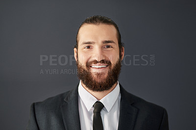 Buy stock photo Studio portrait of a handsome young corporate businessman posing against a grey background