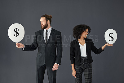 Buy stock photo Studio shot of two young corporate businesspeople holding dollar sign icons against grey background
