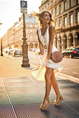 Buy stock photo Shot of a beautiful young woman holding her dress down from the wind while exploring the city of Paris