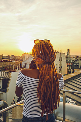Buy stock photo Rearview shot of a young woman standing on a rooftop and taking pictures of the beautiful city of Paris, France