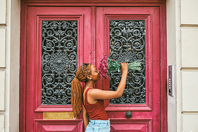 Buy stock photo Shot of an attractive young woman smelling her bouquet of flowers in front of a doorway in Paris, France