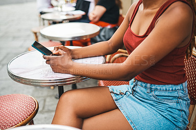 Buy stock photo Cropped shot of an unrecognizable woman using her cellphone while relaxing at an outdoor cafe in Paris, France