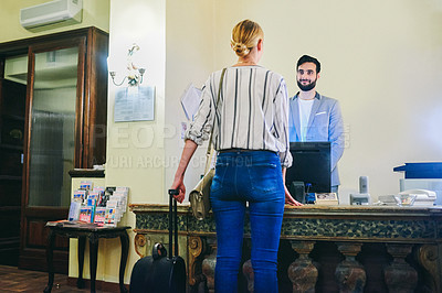 Buy stock photo Cropped shot of a handsome young male receptionist receiving a female visitor at a hotel front desk