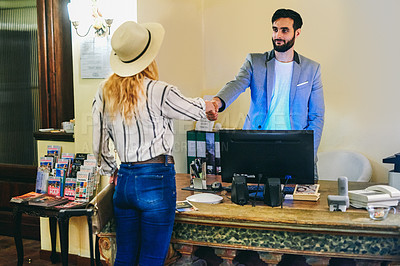 Buy stock photo Cropped shot of a handsome young male receptionist shaking hands with a female visitor at the front desk of a hotel
