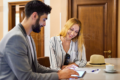 Buy stock photo Shot of two young businesspeople using a digital tablet during their meeting inside a coffeeshop