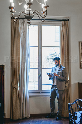 Buy stock photo Full length shot of a handsome young businessman using a digital tablet while standing inside his hotel room