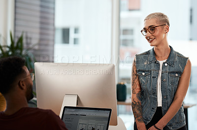 Buy stock photo Shot of an attractive young businesswoman having a discussion with her colleague inside a modern office