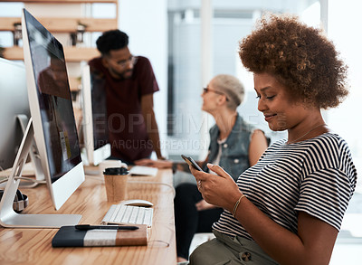 Buy stock photo Shot of an attractive young creative businesswoman using her cellphone while working in an office with colleagues in the background