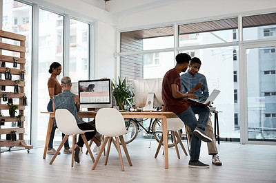 Buy stock photo Full length shot of two young businessmen using a laptop together inside a modern office with colleagues in the background