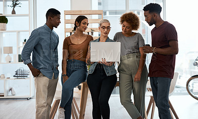 Buy stock photo Shot of a group of young businesspeople using a laptop together inside a modern office