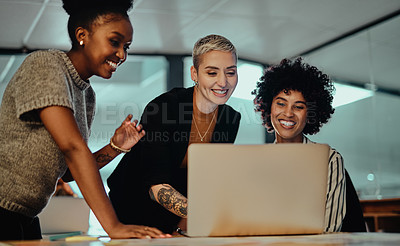 Buy stock photo Shot of a group of businesswomen working together on a laptop in an office at night
