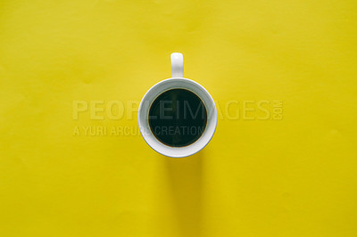 Buy stock photo High angle shot of a cup of coffee on a yellow background