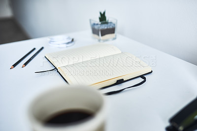 Buy stock photo Shot of an open notebook surrounded by stationery on a desk at home