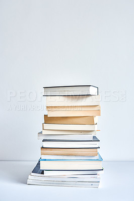 Buy stock photo Shot of a pile of books stacked up on a table