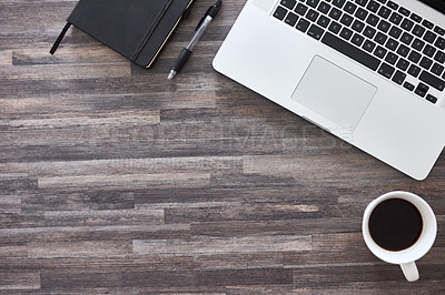 Buy stock photo Shot of a laptop, notebook and cup of coffee on a work desk