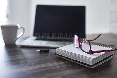 Buy stock photo Shot of notebooks and glasses on a desk with a laptop in the background