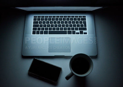 Buy stock photo Shot of a laptop, smartphone and cup of coffee on a work desk at night