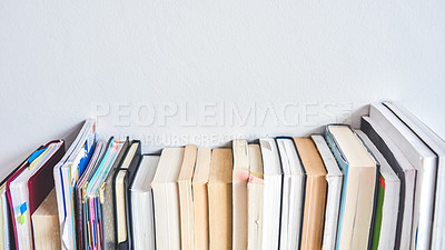 Buy stock photo Shot of a row of books lined up against a wall