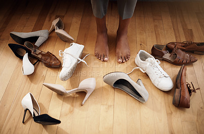 Buy stock photo Cropped shot of an unrecognizable woman trying on various shoes at home