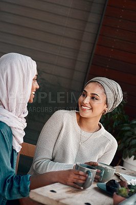 Buy stock photo Cropped shot of two affectionate young girlfriends having a chat at a coffee shop while dressed in hijab