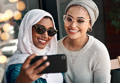 Buy stock photo Cropped shot two affectionate young girlfriends taking a selfie together at a cafe while dressed in hijab