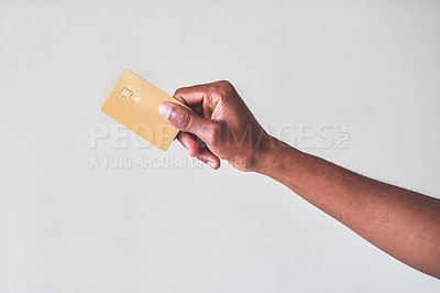 Buy stock photo Cropped shot of an unrecognizable man holding up his credit card against a grey background
