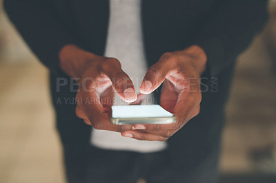 Buy stock photo Cropped shot of an unrecognizable man using a smartphone while sitting indoors